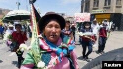 """Pendukung mantan Presiden Bolivia Evo Morales berpartisipasi dalam pawai di Cochabamba, Bolivia, 16 November 2019. Tanda itu berbunyi """"Militer tidak membunuh orang"""". (Foto: Reuters/Danilo Balderrama)"""