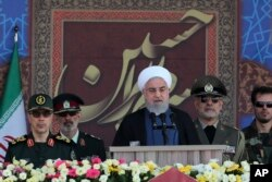 President Hassan Rouhani speaks at a military parade marking 39th anniversary of outset of Iran-Iraq war, in front of the shrine of the late revolutionary founder Ayatollah Khomeini, just outside Tehran, Sept. 22, 2019.
