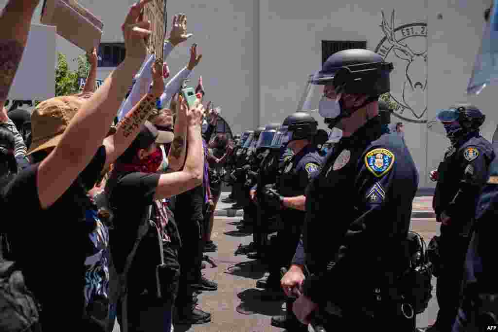 Demonstrators face-off with officers in front of the San Diego Police in downtown San Diego, California on May 31, 2020, as they protest the death of George Floyd.