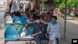 People sit in waiting area of the Benazir Hospital ignore social distancing, during a lockdown to contain the spread of coronavirus, in Rawalpindi, Pakistan, Wednesday, April 22, 2020. (AP Photo/B.K. Bangash)