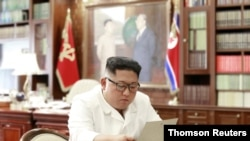 North Korean leader Kim Jong Un reads a letter from U.S. President Donald Trump, in Pyongyang, North Korea, in this picture released by North Korea's Korean Central News Agency, June 22, 2019.