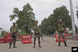 FILE - Indian paramilitary soldiers stand guard near a temporary checkpoint on the road leading toward an Independence Day parade venue during a lockdown in Srinagar, Indian-controlled Kashmir, Aug. 15, 2019.