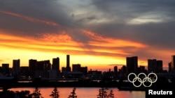 Cincin Olimpiade dengan latar gedung pencakar langit saat matahari terbenam di Tokyo, Jepang, 20 Juli 2021.