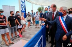 French Prime Minister Jean Castex, second right, and the mayor of Anglet, Claude Olive, right, look at people lining up to get vaccine shots in Anglet, southwestern France, July 17, 2021.