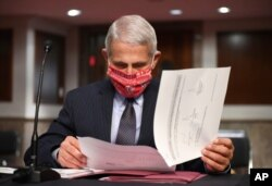 In this Tuesday, June 30, 2020 file photo, Dr. Anthony Fauci, director of the National Institute for Allergy and Infectious Diseases, prepares to testify before a Senate Health, Education, Labor and Pensions Committee hearing on Capitol Hill…