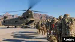 FILE - U.S. soldiers load onto a Chinook helicopter to head out on a mission in Afghanistan, Jan. 15, 2019.