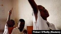 Des enfants lèvent la main pendant une leçon dans une école de Kinshasa, capitale de la République démocratique du Congo, le 20 novembre 2006. REUTERS/Finbarr O'Reilly