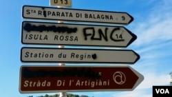 Graffiti supporting Corsica's FLNC liberation movement covers a road sign in the island's Balagne region. (Lisa Bryant/VOA)