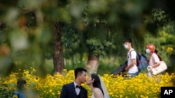 FILE - People wearing face masks pass by newlyweds kissing as they pose for wedding photos at the Olympic Forest Park in Beijing on July 2, 2020.