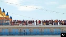 FILE - Passengers of the Costa Deliziosa cruise ship wait to disembark in the port of Genoa, Italy, April 22, 2020.