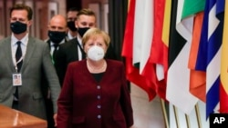 German Chancellor Angela Merkel leaves during as officials depart at the end of an EU summit in Brussels, Belgium, Oct. 16, 2020.