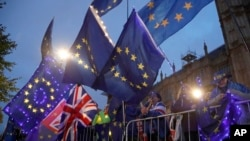 Pro European Union protesters wave flags opposite parliament in London, Sept. 9, 2019. British Prime Minister Boris Johnson voiced optimism Monday that a new Brexit deal can be reached so Britain leaves the European Union by Oct. 31.