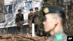 In this Nov. 27, 2017, file photo, North Korean soldiers look at the South side as a South Korean stands guard near the spot where a North Korean soldier crossed the border on Nov. 13 at the Panmunjom, in the Demilitarized Zone, South Korea.