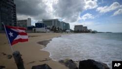 Bendera Puerto Rican berkibar di tepi pantai yang sepi di Ocean Park, San Juan, Puerto Rico, 21 Mei 2020.