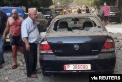 Un hombre herido camina junto a un auto dañado en una calle, luego de la explosión en Beirut.