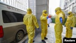 Petugas rumah duka (mengenakan pakaian pelindung), membantu koleganya menyemprotkan pembasmi kuman seusai memindahkan jenazah pasien yang terinfeksi virus corona dari rumah sakit di Wuhan, provinsi Hubei, China, 30 Januari 2020.