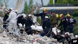 救援人員將一名遇難者的屍體抬出廢墟。