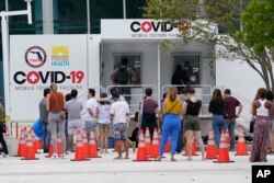 People line up at a COVID-19 rapid test site, Nov. 7, 2020 in Miami Beach, Fla.