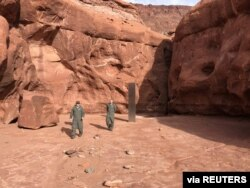 Utah Department of Public Safety Aero Bureau and Utah Division of Wildlife Resources crew members walk near a metal monolith they discovered in a remote area of Red Rock Country in Utah, Nov. 18, 2020.