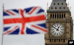 """FILE - British Union flag waves in front of the Elizabeth Tower at Houses of Parliament containing the bell know as """"Big Ben"""" in central London, March 29, 2017."""