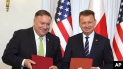 Secretário de Estado, Mike Pompeo, (esq) e ministro polaco da Defesa, Mariusz Blaszczak, após a assinatura do acordo
