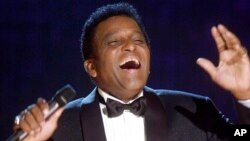 FILE - Charley Pride performs during his induction into the Country Music Hall of Fame at the Country Music Association Awards show at the Grand Ole Opry House in Nashville, Tenn., Oct. 4, 2000.