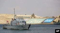 FILE - A cargo ship sails through the town of Ismailia, Egypt, March 30, 2021, as traffic resumed through the Suez Canal after it was blocked by a massive ship that had been stuck sideways for nearly a week.