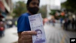 Una mujer muestra un nuevo billete de 500.000 bolívares después de retirarlo de un banco en Caracas, Venezuela, el martes 16 de marzo de 2021.