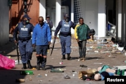 Police officers detain demonstrators during protests following the imprisonment of former South Africa President Jacob Zuma, in Katlehong, South Africa, July 12, 2021.