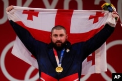 Lasha Talakhadze of Georgia holds his national flag as he celebrates the gold medal he won at the men's +109kg weightlifting event, at the 2020 Summer Olympics in Tokyo, Japan, Aug. 4, 2021.