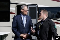 Washington Gov. Jay Inslee, left, talks with with Nathan Weed, incident commander for the coronavirus response team at Department of Health, outside a recreation vehicle at a potential coronavirus isolation and quarantine site, March 4, 2020.