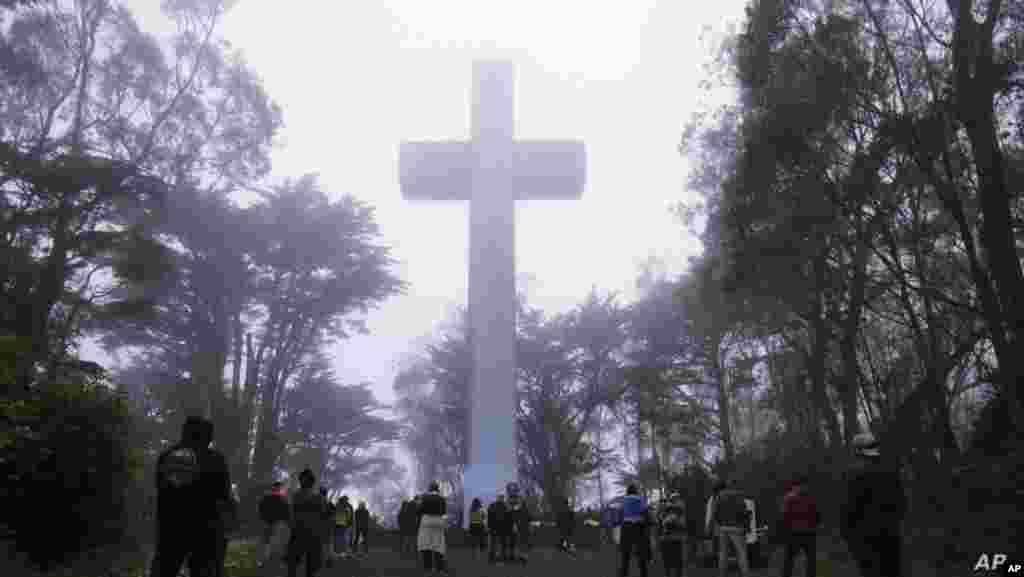 미국 샌프란시스코 마운트 데이비드슨 (Mount Davidson)에서 부활절을 맞아 예정됐던 예배가 '자택 대기령'으로 취소된 가운데 기독교 신자들이 십자가 앞에 모여 있다.