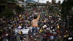 Um acrobata está sobre os manifestantes enquanto eles marcham durante um protesto anti-governamental em Bogotá, Colômbia, 12 de Maio, 2021.