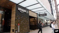 FILE - In this March 4, 2020 file photo, people walk out of an Amazon Go store, in Seattle. Amazon is rolling out a new device for contactless transactions that will scan an individual's palm. The Amazon One, which will initially launch in two…