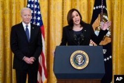 President Joe Biden listens as Vice President Kamala Harris speaks before signing the COVID-19 Hate Crimes Act, in the East Room of the White House, May 20, 2021, in Washington.