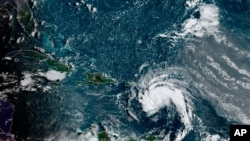 Satellite image provided by the National Oceanic and Atmospheric Administration (NOAA) shows a tropical storm east of Puerto Rico in the Caribbean, at 7:50am EST, Aug. 10, 2021.
