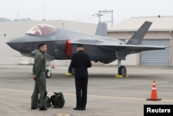 A South Korean fighter pilot, left, stands next to his F-35 stealth fighter during a ceremony to mark the 71st Armed Forces Day at the Air Force Base in Daegu, South Korea, Oct. 1, 2019.