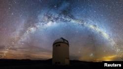 La forma distorsionada del disco estelar de la Vía Láctea se ve sobre el telescopio de la Universidad de Varsovia en el Observatorio Las Campanas, Chile, en una interpretación artística, 1 de agosto de 2019. (Jan Skowron / Universidad de Varsovia).