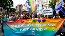 """People march holding a banner that reads """"Do you know who you love? Whoever you want!"""" march during a gay pride parade in Budapest, Hungary, July 24, 2021."""