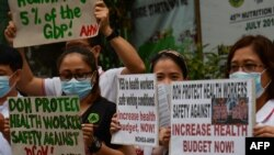 Health workers wearing protective masks carry placards as they hold a protest in front of a government hospital in Manila on February 7, 2020. - The new coronavirus that emerged in the Chinese city of Hubei to date has killed more than 630 people,…