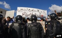 Security forces confront protesters from the Ettadhamen city suburb on the northwestern outskirts of Tunisia's capital Tunis, Jan. 26, 2021.