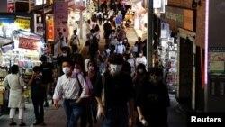 Personas con máscaras protectoras, en medio del brote de la enfermedad por coronavirus, se dirigen a un distrito comercial en Tokio, Japón, el 28 de julio, 2021.