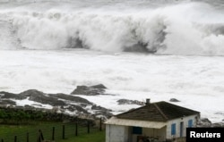 FILE - A wave breaks in front of a house on the coast of La Guardia, northern Spanish region of Galicia, Feb. 6, 2014.