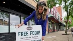 Coleen Piteo, direktur pemasaran dari restoran Yours Truly di Chagrin, Ohio, AS, memasang papan pengumuman lowongan pekerjaan untuk restorannya pada 3 Juni 2021. (Foto: AP/Tony Dejak)