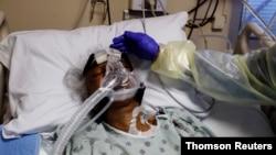 Medicinska sestra Alma Abad dodiruje glavu pacijenta oboljelog od koronavirusa, na odjeljenju Intenzivne njege u bolnici Roseland, u južnom delu Chicaga,, Illinois.