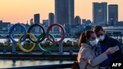 Dua orang yang mengenakan masker mengambil swafoto di depan Olympic Rings, di taman Odaiba Seaside, Tokyo yang akan menjadi lokasi Olimpiade 2020 (foto: dok).