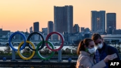 People wear face masks as they take pictures in front of the Olympic Rings at the Odaiba Seaside Park in Tokyo on March 6, 2020. - Construction of all new permanent venues for the Tokyo 2020 Olympics and Paralympics is now complete, organisers said…