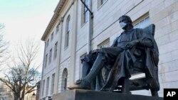 La estatua de John Harvard, en la prestigiosa universidad que lleva su nombre, fue decorada con una mascarilla en los días más críticos de la pandemia. Ahora la universidad se prepara para recibir a una parte de sus estudiantes.