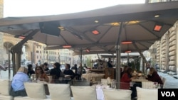 Bars and restaurants have gone back to being populated in Florence and many are enjoying their capuccinos sitting in the sun at the tables outside. (Sabina Castelfranco/VOA)