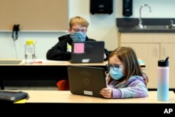 FILE - Students wear masks as they work in a fourth-grade classroom at Elk Ridge Elementary School in Buckley, Wash., Feb. 2, 2021.